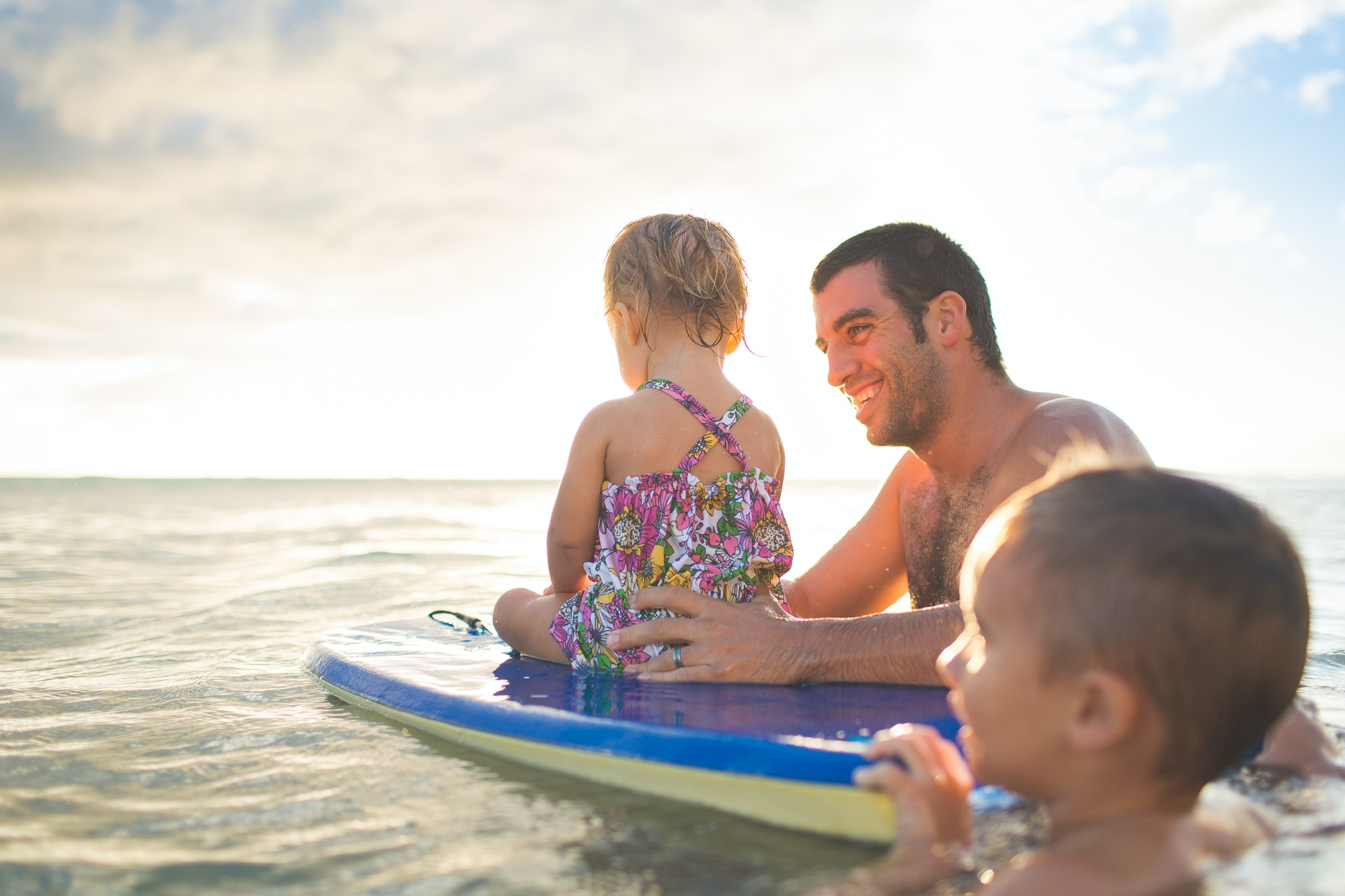 Dad and kids on boogie board in the ocean